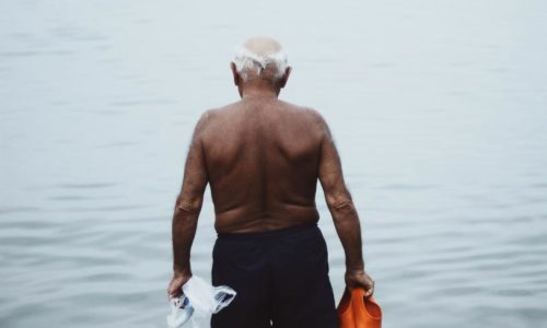 Old man fishing for mussels at sea.
